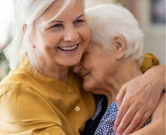 Two elderly people embrace