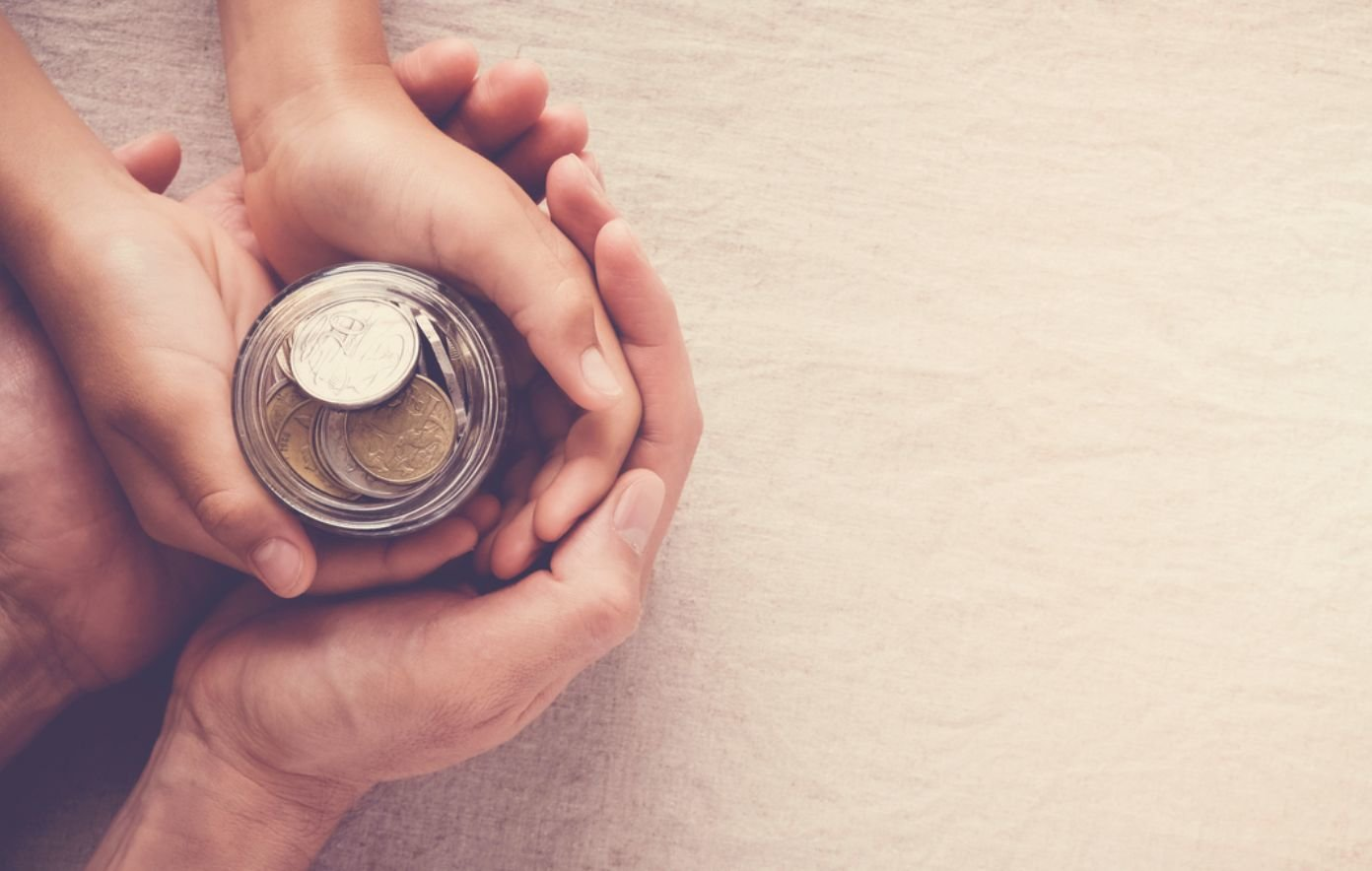 A child and an adult hold a coin jar