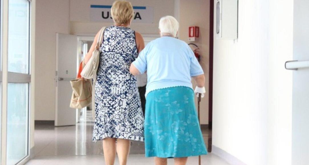 Two people walk in a hospital hallway