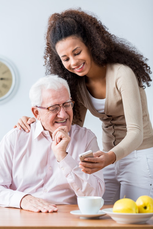 A woman shows an older man her phone