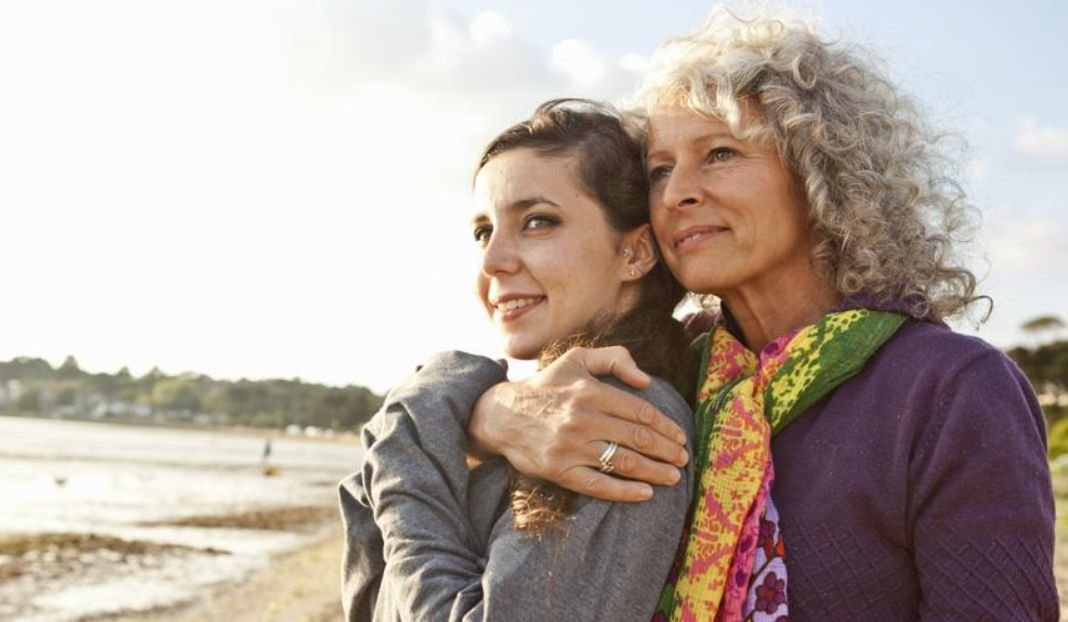 Two women embrace while looking out
