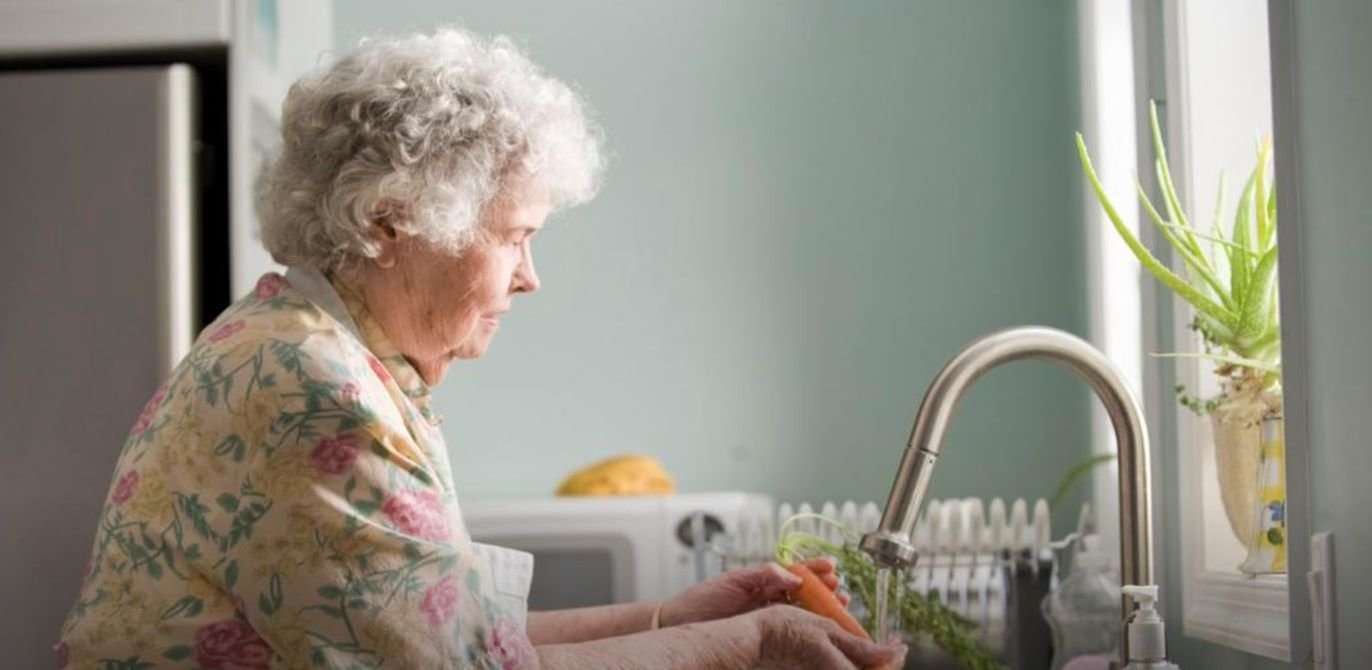 A woman washes some carrots