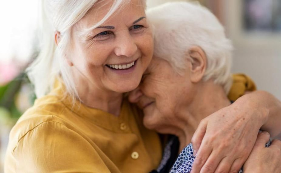 Two women embrace while smiling