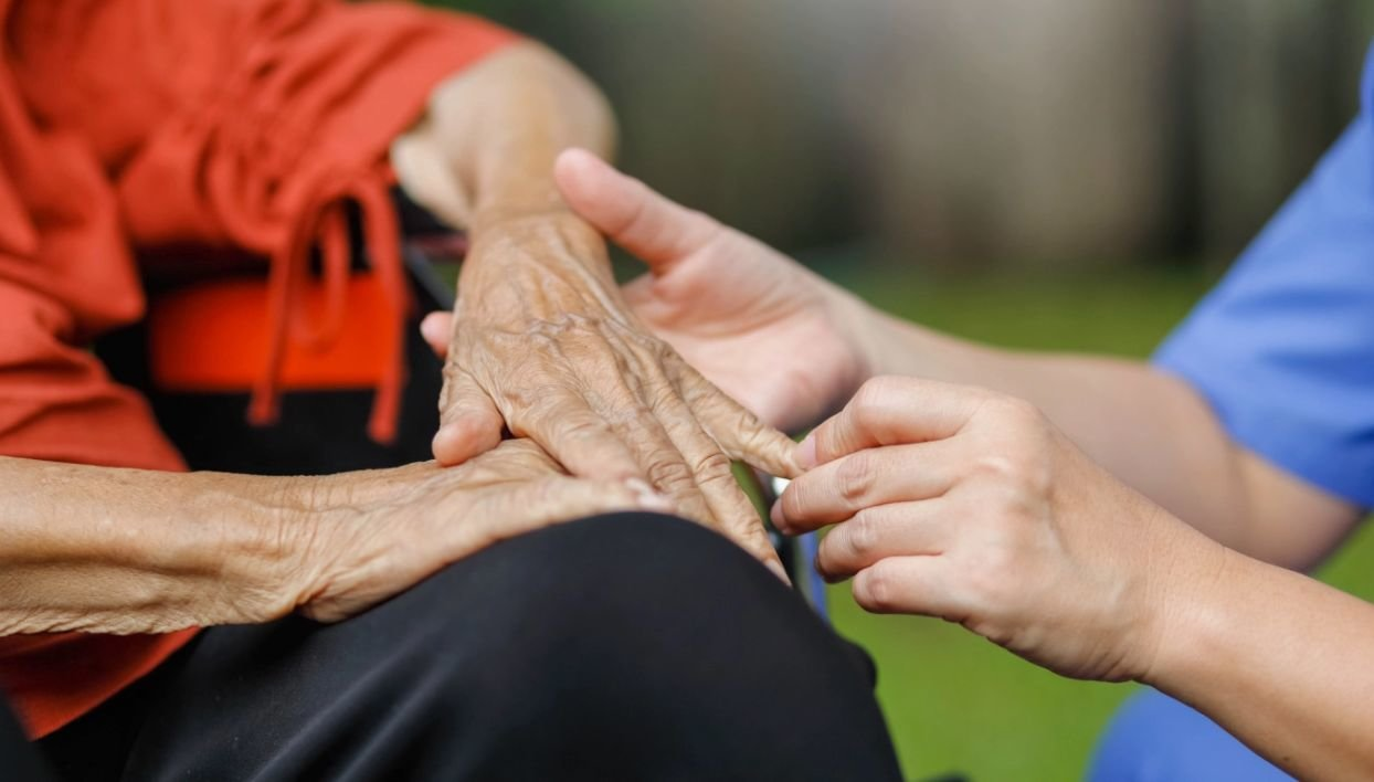 Two people sit while clasping hands